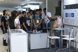 Marcelo Essado apresentando aos visitantes o modelo de engenharia do NanosatC-BR1 e o projeto de inovação em kits didáticos aeroespaciais.